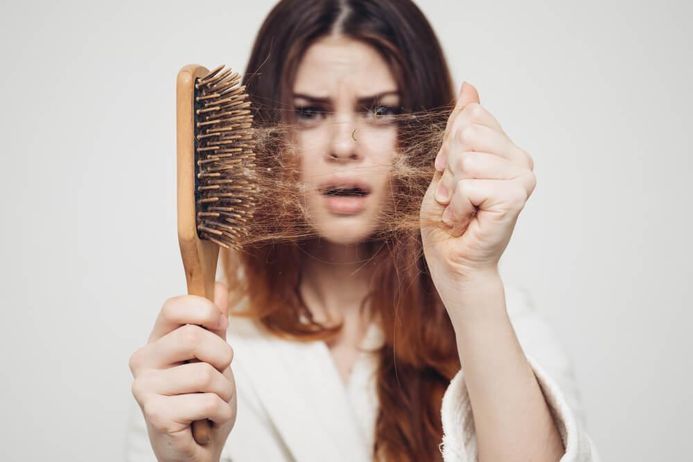 Na foto uma moça com cabelos longos segurando uma escova cheia de  cabelos com cara de espanto