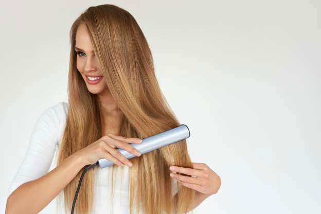 na imagem uma mulher loira de cabelos sorridente está segurando uma chapinha na ponta dos fios. Ela está sorridente e olhado para o lado.  Veja os maiores Erros ao fazer a chapinha